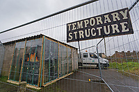 "Pictured: A ""Temporary Structure"" sign on the fence protecting the Banksy graffiti on a garage in Port Talbot, Wales, UK. Tuesday 25 December 2018<br /> Re: The artist Banksy has confirmed that a new graffiti piece that has appeared in Port Talbot, south Wales is his.<br /> He announced on Instagram: ""Season's greetings"" - with a video of the artwork in the Taibach area of Port Talbot.<br /> The image appears on two sides of a garage in a lane near Caradog Street, depicting a child enjoying snow falling - the other side reveals it is a fire emitting ash.<br /> The owner of the garage said he had not slept over fears it might be vandalised."