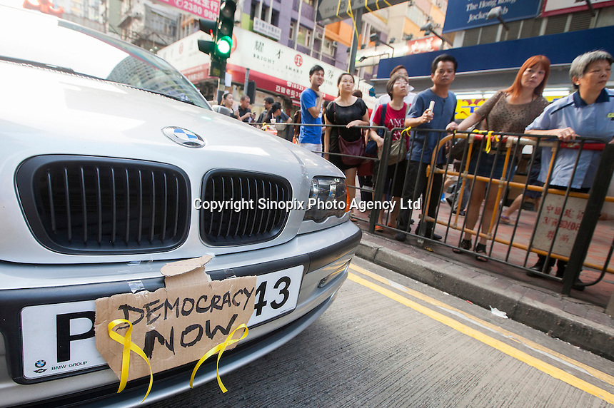 A stranded car with a democracy slogan sits in the middle of an interesction controlled by protesters in Mong Kok, on the second day of the mass civil disobedience campaign Occupy Hong Kong, Mong Kok, Kowloon, Hong Kong, China, 30 September 2014. The movement is also being dubbed the 'umbrella revolution' after the versatile umbrellas used to shield protesters from rain, sun - and police pepper spray.