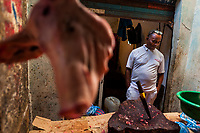 An Afro-Colombian butcher waits for customers in his stand in the market of Bazurto in Cartagena, Colombia, 19 December 2017. Far from the touristy places in the walled city, a colorful, vibrant labyrinth of Cartagena's biggest open-air market sprawls to the Caribbean seashore. Here, in the dark and narrow alleys, full of scrappy stalls selling fruit, vegetables and herbs, meat and raw fish, with smelly garbage on the floor and loud reggaeton music in the air, the African roots of Colombia are manifested.