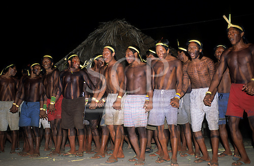 Bacaja village, Amazon, Brazil. Young men dance and sing holding hand at a nighttime celebration; Xicrin tribe.