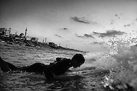 21 year old surfer Mahmoud Alyrashi paddles out through the waves in the Mediterranean Sea.