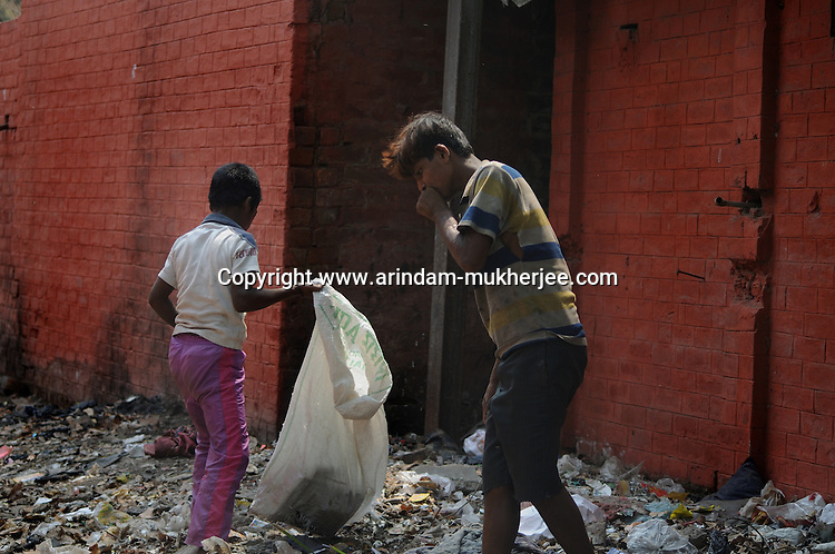 Alamgir and his mate Abhijit scavanging for goods on a city dumpyard. The boys earn money by selling plastic botlles and goods they collect from the compartment when these empty of passengers and city dumpyards. They  buy drugs and dendrite adhesive with any money they get from pick pocketing. The Sealdah terminus station area is home to a thriving trade in narcotics. Calcutta, West Bengal, India. Arindam Mukherjee