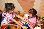 Education preschool 3-4 year olds group of three girls pretend play together in family area playing with toy food