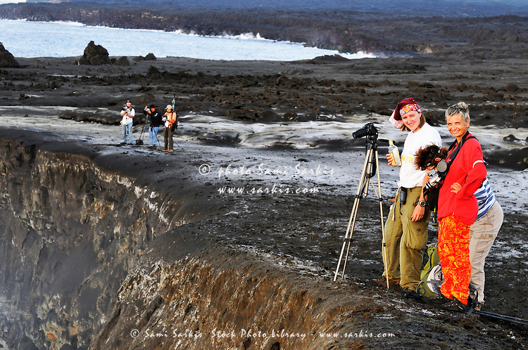 Group of tourists on crater edge watching molten lava flowing to the sea, Kilauea Volcano, Hawaii Islands, United States