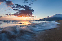 Waves breaking at a tranquil sandy beach minutes before sunset on Maui.
