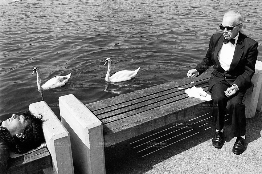 Switzerland. Zürich. An old man is dressed with a black tuxedo and bow tie. The elderly man wearing black sunglasses, seated on a wood bench close to the lake, gives bread to two swans. Another man lays on his back and sleeps. © 1988 Didier Ruef