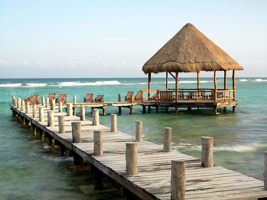 Mexico, Quintana Roo, Yucatan Peninsula, Akumal Mayan Riviera, pier with palapa jutting out to the water from the beach.