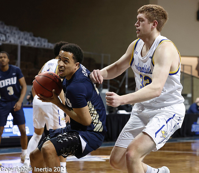 SIOUX FALLS, SD - MARCH 8: Sheldon Stevens #23 of the Oral Roberts Golden Eagles drives pat Matt Dentlinger #32 of the South Dakota State Jackrabbits during the Summit League Basketball Tournament at the Sanford Pentagon in Sioux Falls, SD. (Photo by Richard Carlson/Inertia)