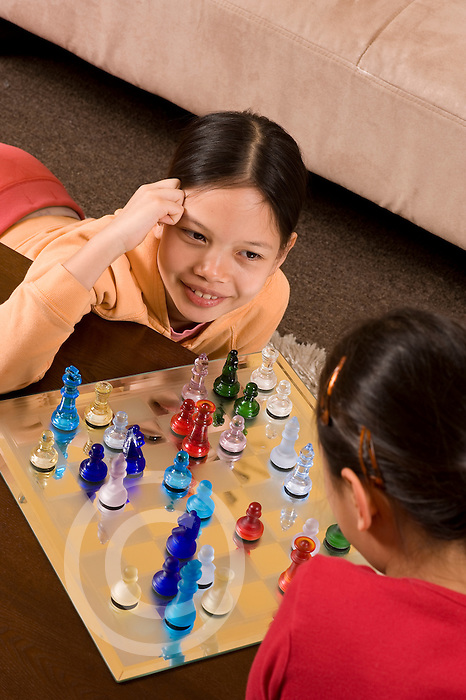 9 year old girl playing chess with 8 year old friend Filipina and Vietnamese American vertical using glass chess set