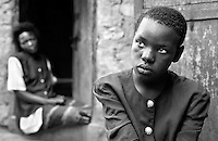 A teenage girl and her mother sit outside their house in Kampala, Uganda on April 28, 2001. The mother is very ill with AIDS. More than 13 million African children have been orphaned by the the AIDS pandemic. Worldwide, more than 20 million people have died since the first cases of AIDS were identified in 1981.
