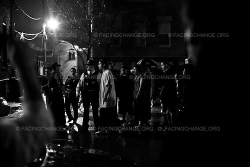 Chicago Illinois, USA<br /> 2009 May<br /> <br /> Chicago police attend to a crime scene where a 21-year-old man was shot and killed inside his car. Friends on the block stare as paramedics took the body away.