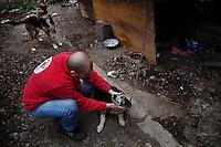 """BULGARIA, Sofia, 2012/04/13..Yavor Gechev, marketing director of the animal welfare organization """"Four Paws"""" (Four Paws) embraces the watchdog in an open parking in the center of Sofia, Bulgaria during a vaccination operation and injection ID chip..BULGARIE, Sofia, 2012/04/13..Yavor Gechev, directeur marketing de l'organisation de protection des animaux """"Four Paws"""" (Quatre Pattes) étreint le chien de garde d'un parking ouvert dans le centre de Sofia, Bulgarie lors d'une opération de vaccination et d'injection de puce d'identification..© Pierre Marsaut"""