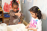 Education Preschool  3 year olds two girls playing separately at sand table