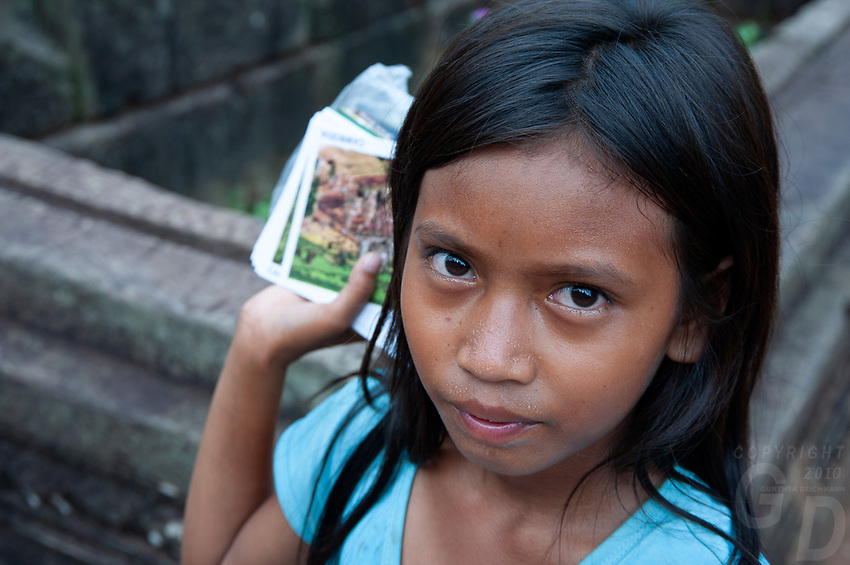 A local Khmer girl vender selling her souvenirs at theEast Mebona 10th Centurytempleat Angkor, Cambodia. Built during the reign of King Rajendravarman,Interesting are the carved standing Elephants on the corners. Cambodia Local Khmer girl, vendor