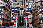 Interior large warehouse of freight stacked high. Woman on forklift retrieves freight.
