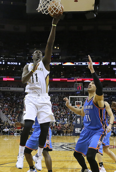 New Orleans Pelicans guard Jrue Holiday (11) shoots over Oklahoma City Thunder center Enes Kanter (11) during the first half of an NBA basketball game Thursday, Feb. 25, 2016, in New Orleans. The Pelicans won 123-199. (AP Photo/Jonathan Bachman)