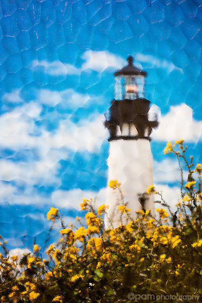 Yellow flowers in front of Oregon lighthouse taken under textured glass