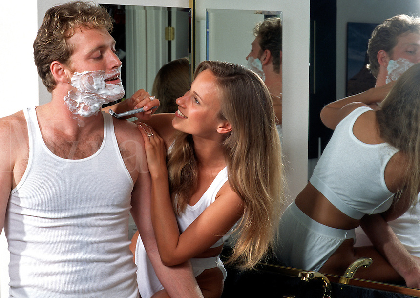 A smiling young couple at home having fun shaving.