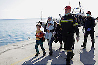 Pictured: A young mother is escorted to safety by a member of the emrgency services Thursday 27 November 2014<br />
