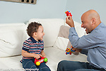 Toddler boy age 18 months at home with father playing with toy airplanes