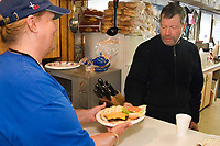 Volunteer serves up hot meal to musher @ Takotna Chkpt Takotna Alaska 2006 Iditarod Winter