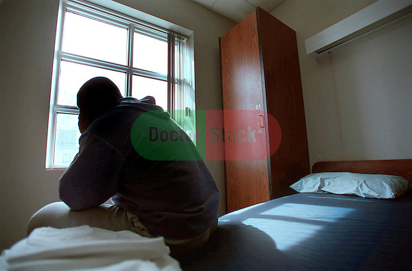silhouette of fatigued male patient sitting on edge off bed in dorm room of drug treatment center