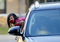 Liberty Strickland, a second grade student at The New School, leans out of the car Thursday, October 1, 2020, before she is dropped off at the school for a day of classes in Fayetteville. Check out nwadg.com/photos for a photo gallery.(NWA Democrat-Gazette/David Gottschalk)