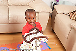 12 month old baby boy smiling hugging blanket after peek a boo game horizontal