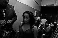 """A female Lucha libre wrestler Sahori walks out in the backstage for her fight at a local arena in Mexico City, Mexico, 30 April 2011. Lucha libre, literally """"free fight"""" in Spanish, is a unique Mexican sporting event and cultural phenomenon. Based on aerial acrobatics, rapid holds and the use of mysterious masks, Lucha libre features the wrestlers as fictional characters (Good vs. Evil). Women wrestlers, known as luchadoras, often wear bright shiny leotards, black pantyhose or other provocative costumes. Given the popularity of Lucha libre in Mexico, many wrestlers have reached the cult status, showing up in movies or TV shows. However, almost all female fighters are amateur part-time wrestlers or housewives. Passing through the dirty remote areas in the peripheries, listening to the obscene screams from the mainly male audience, these no-name luchadoras fight straight on the street and charge about 10 US dollars for a show. Still, most of the young luchadoras train hard and wrestle virtually anywhere dreaming to escape from the poverty and to become a star worshipped by the modern Mexican society."""