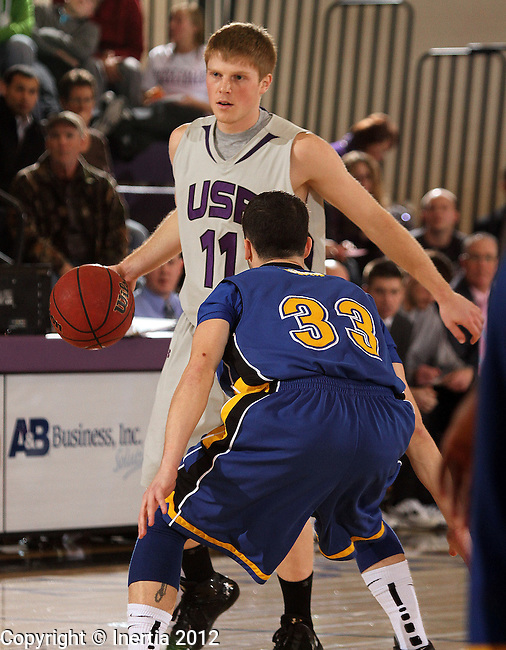 SIOUX FALLS, SD - JANUARY 17:  Derek Brown #11 from the University of Sioux Falls looks to  drive around Jesse Bean #33 from Dakota State University in the first half of their game Tuesday night at the Stewart Center. (Photo by Dave Eggen/Inertia)