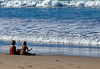Ten year old girl and seven year girl sitting in the sand at the edge of ocean. United States Pacific Coast Beach.