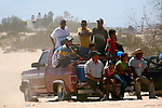 12 people cram into rear of truck to watch the sand dune auto competitions