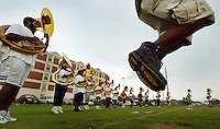 Bethune-Cookman College Marching Wildcat Band tuba player Randy Faulk, feet at right, jumps high in the air as the tuba section plays scales while jumping in place during practice Friday afternoon, Aug. 27, 2004, on campus in Daytona Beach, Fla. The exercises are intended to prepare the tuba section for the intricate dance and music performances they will perform during their upcoming halftime shows. (AP Photo/Daytona Beach News-Journal, Kelly Jordan)