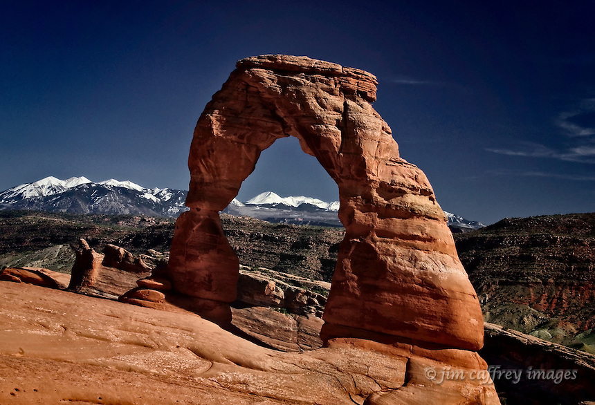 Delicate Arch in Arches National Park near Moab, Utah with the snow covered La Sal Mountains in the distance.