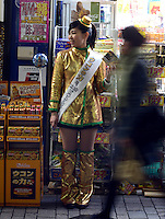 "Young girl in Gold outfit is advertising ""Ukon no Chikara"" (Power of turmeric) which is effective for hangover in front of drug store in Shinjuku, Tokyo"