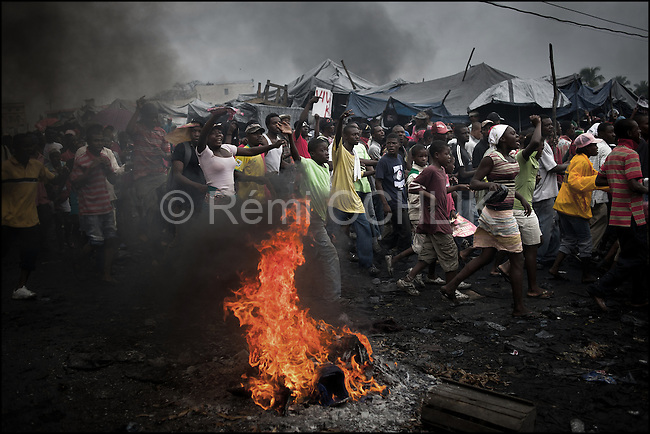 """© Remi OCHLIK/IP3 - Port au Prince on 2010 december 9 - PORT-AU-PRINCE -- Clashes and shooting were reported Thursday in Haiti's capital for a second day as demonstrators staged a march to protest what they said was election fraud in the Nov. 28 presidential elections..The protests broke out Wednesday after election officials announced Tuesday night that two candidates had made it into a runoff: Mirlande Manigat, a former first lady, and Jude CÈlestin, the candidate of current President RenÈ PrÈval's party. Out of the running was Michel """"Sweet Micky'' Martelly, who early results had shown running second. - Martelly supporters demonstrate in Petion Ville and set up roadblocks on Delmas street."""
