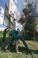 Des jeunes et leurs parents a l'aide de 2 engins, installent de grand panneau aux entrees du village