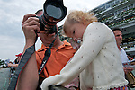 1 August 10: Eric Ramos, of Brooklyn, NY, holds his daughter Elizabeth, 2, with one arm, as he mans the rail hoping to get a photo of at least one famous horse on Haskell Invitational Day at Monouth Park in Oceanport, New jersey