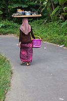 Borobudur, Java, Indonesia.  Village Woman Carrying Tray on Head.