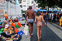 Carioca´s lifestyle. A young multi-ethnic couple going to Copacabana beach passes through 2013 World Youth Day ( WYD ) participants that are resting and eating in sidewalk, an event for young people organized by the Catholic Church in Rio de Janeiro, Brazil.
