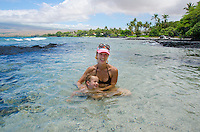 A local mom and her son smile while playing in a tide pool at a beach in Puako, South Kohala, Big Island.
