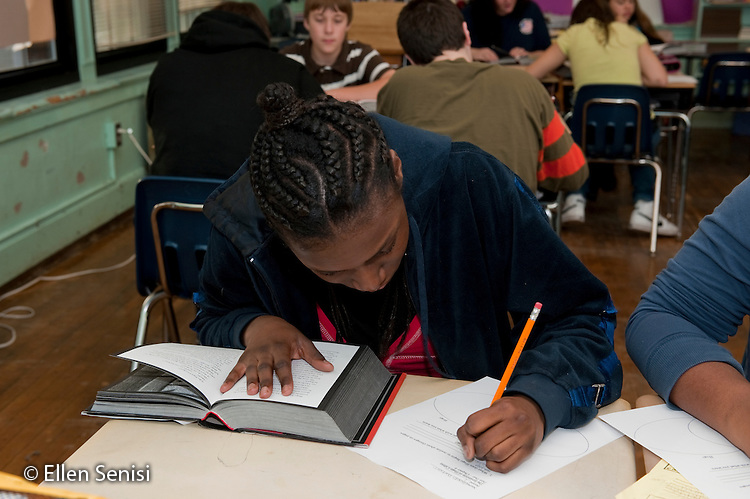 MR / Schenectady, New York. Oneida Middle School (urban public school). 8th grade English class. Student (girl; 13) takes notes on book she is reading in class during classroom silent reading time. MR: Dur4. ID: AJ-g8b. © Ellen B. Senisi
