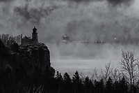 """""""The Ghost and the Lighthouse""""<br /> Lake Superior paints stunning visual drama during the winter months. In December, I eagerly layered-up to enjoy a breathtaking day of photography along Lake Superior's North Shore. The morning got off to a memorable start when the thousand foot Burns Harbor vessel quietly glided through the thick sea smoke by Split Rock Lighthouse just before daybreak. It was worth braving the -24° air temperature to witness this scene. It caused me to wonder about the many tales the lighthouse could tell about the unforgiving lake and those she has challenged."""