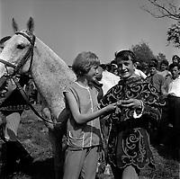 Village de Bourg-Saint-Bernard (Haute-Garonne). Le 18 Mai 1964. Vue d'un couple près d'un cheval dans le pré de la Fadaise.