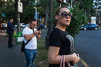 """Armenia. Yerevan. Town center. Lilit Martirosyan stands and waits to cross a road in the town center. She holds her Samsung smartphone in her hand and carries a pink purse on her right arm. She is a transgender woman and a civil rights activist fighting for the rights of trans people in Armenia. On her right arm, a tattoo with the words """" All Equal All Different"""". Lilit Martirosyan is the founder and the president of the NGO called """"Right Side"""", founded in 2016 to defend and fight for the rights of the trans community in Armenia. She became on April 5th 2019 the first member of her country's lesbian, gay, bisexual, transgender and intersex (LGBTI) community to deliver a speech on the parliamentary podium, speaking out against discrimination at a session of its committee on human rights. A trans woman (sometimes trans-woman or transwoman) is a woman who was assigned male at birth. Trans women may experience gender dysphoria and may transition; this process commonly includes hormone replacement therapy and sometimes sex reassignment surgery, which can bring immense relief and even resolve gender dysphoria entirely. Yerevan, sometimes spelled Erevan, is the capital and largest city of Armenia. 1.10.2019 © 2019 Didier Ruef"""