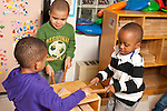 Education preschool 4 year olds group of three boys playing a game with wooden block struction they built hitting top with cylinder blocks