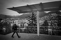 "Switzerland. Canton Ticino. Lugano. A man wearing a mask on the face to protect himself from Coronavirus (also called Covid-19) walks by a bus stop at the railway station. Nobody is waiting for the platform. Due to the spread of the coronavirus, the Federal Council has categorised the situation in the country as ""extraordinary"". It has issued a recommendation to all citizens to stay at home, especially the sick and the elderly. The Federal Council (German: Bundesrat, French: Conseil fédéral, Italian: Consiglio federale, Romansh: Cussegl federal) is the seven-member executive council that constitutes the federal government of the Swiss Confederation. From March 16 the government ramped up its response to the widening pandemic, ordering the closure of bars, restaurants, sports facilities and cultural spaces. Only businesses providing essential goods to the population – such as grocery stores, bakeries and pharmacies – are to remain open. 27.03.2020 © 2020 Didier Ruef"