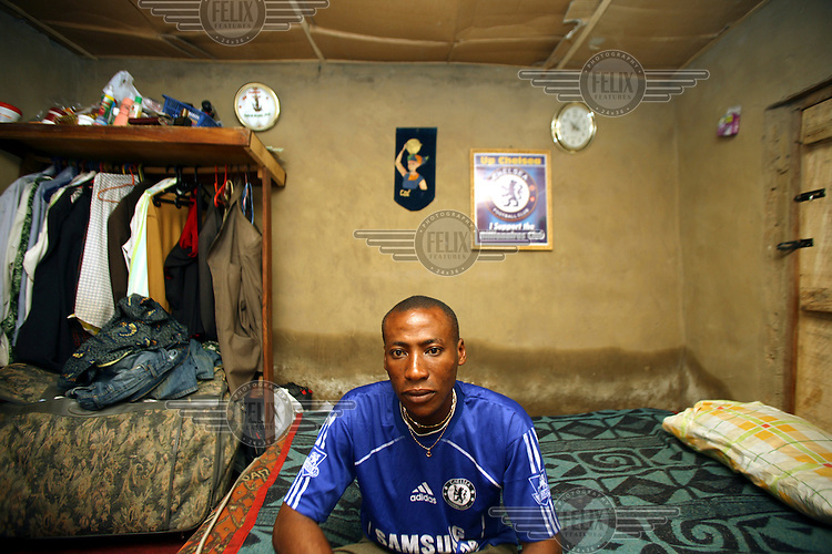 A Chelsea supporter sits inside his house in Abuja. There are more African players playing in European football leagues then ever before, leading to a decline in interest in local leagues, with fans favouring the more lucrative and 'exciting' European leagues.