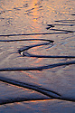 Tidal mudflats in the Humber estuary reflecting the setting sun. East Yorkshire, England, UK.