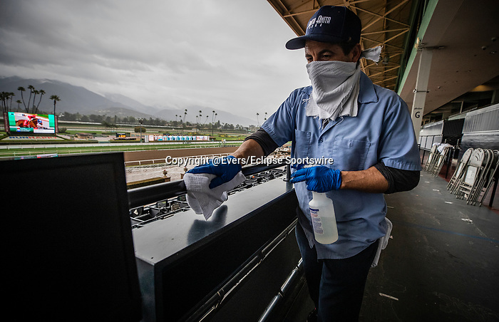 MAR 14: An unidentified worker sanitizes the grandstand handrails despite being closed to the public for safety concerns over the coronavirus in Arcadia, California on March 14, 2020. Evers/Eclipse Sportswire/CSM
